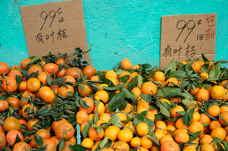 Piles of oranges at an outdoor store. by Lucas Saugen for Stocksy United
