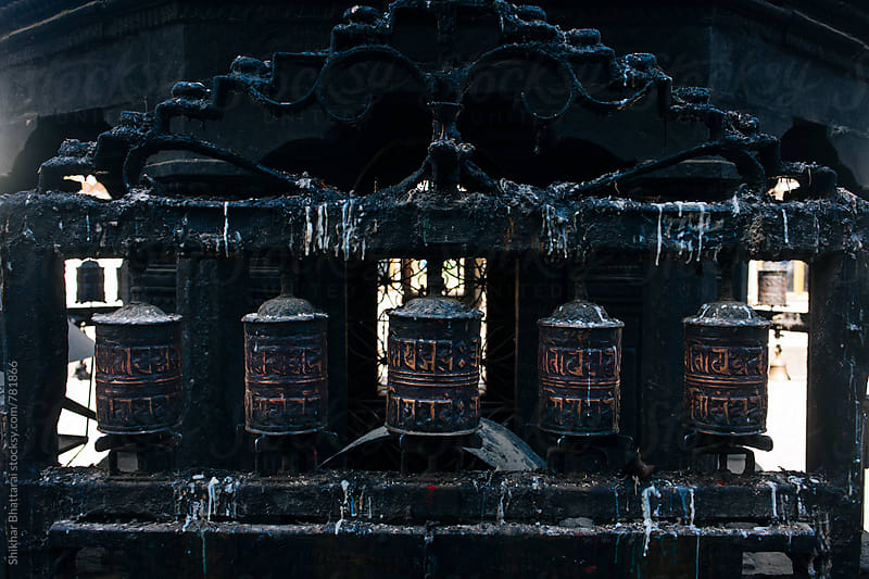 Old moulded prayer wheels covered in wax outside a temple in Nepal. by Shikhar Bhattarai for Stocksy United
