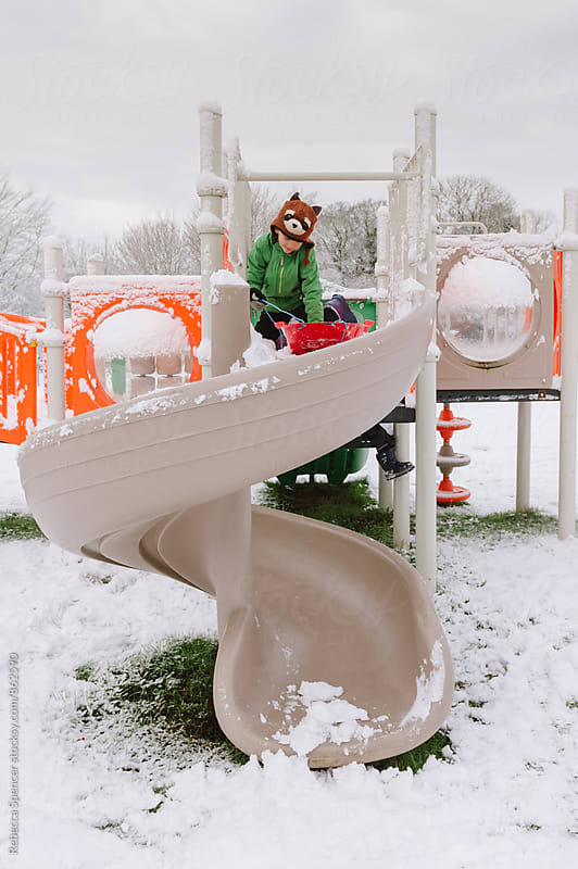 Daring child prepares to ride his sledge down a slide by Rebecca Spencer for Stocksy United