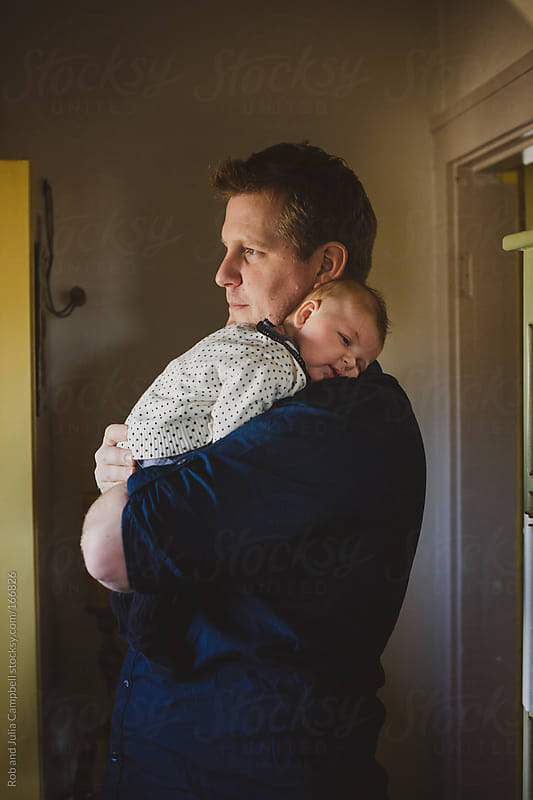 Young dad enjoying his sleeping baby daughter by Rob and Julia Campbell for Stocksy United