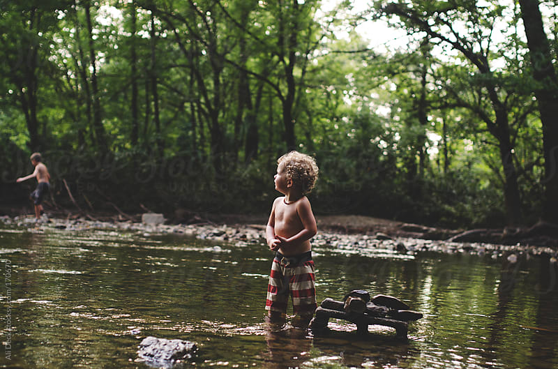 A Toddler Looks for Rocks by Ali Deck for Stocksy United