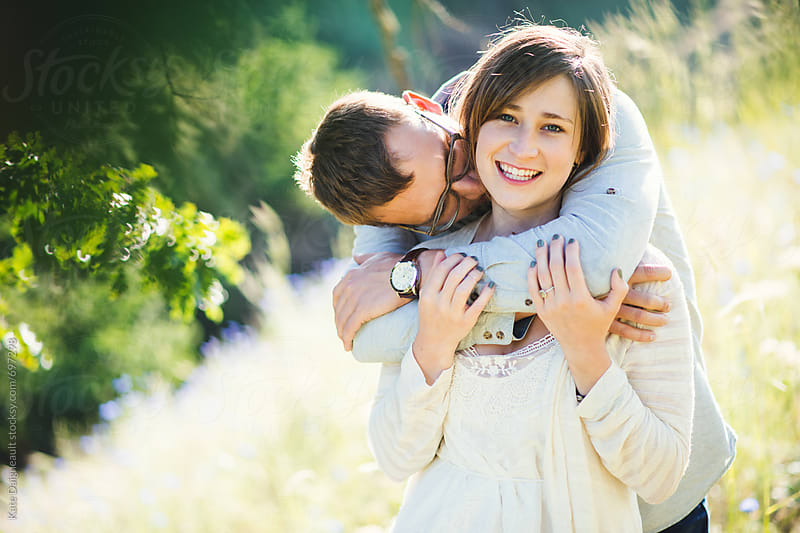 Attractive young couple embracing on a sunny hillside. by Kate Daigneault for Stocksy United
