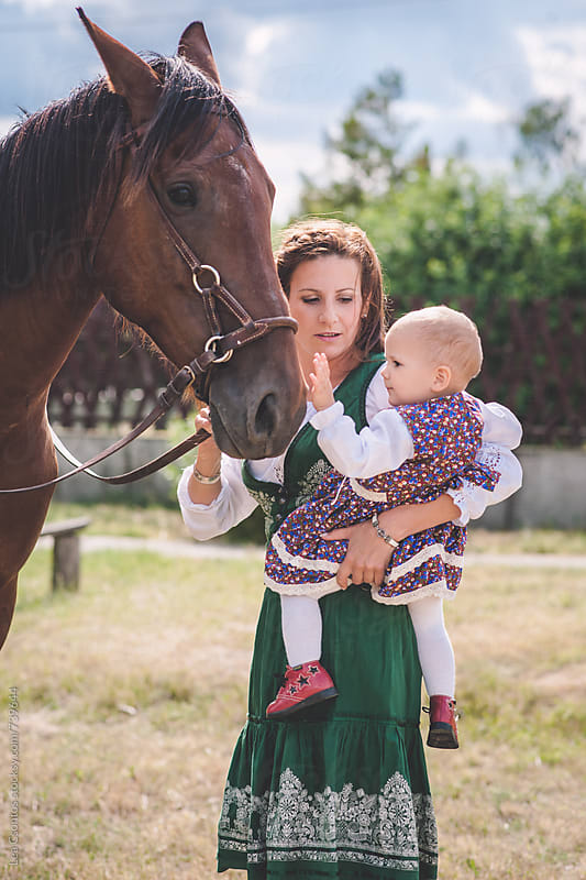 Child held by her mother caressing a horse. by Lea Csontos for Stocksy United