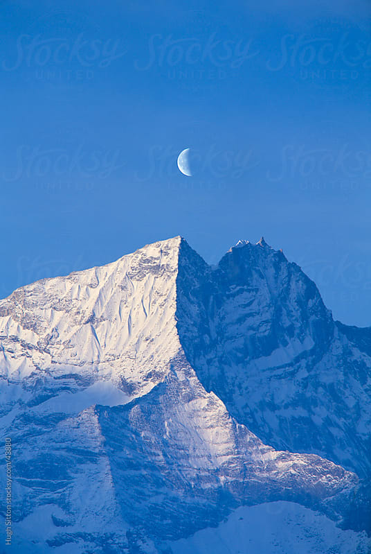 Moon rising over snow covered mountain. by Hugh Sitton for Stocksy United