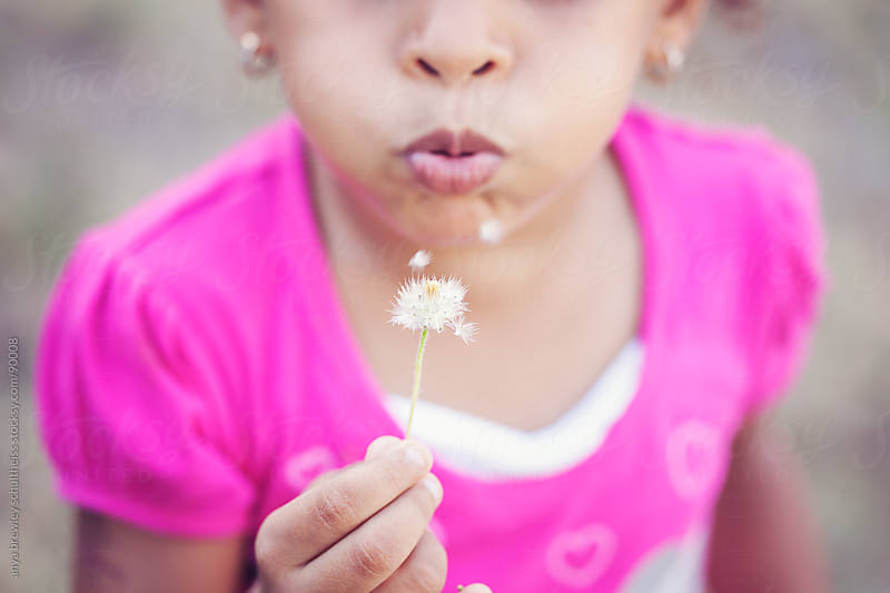 Closeup portrait of a young girl blowing a dandelion puff by anya brewley schultheiss for Stocksy United