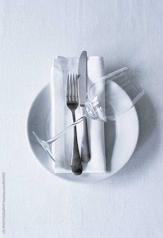 Empty white plate with cutlery on napkin and wine glass on tablecloth by J.R. PHOTOGRAPHY for Stocksy United