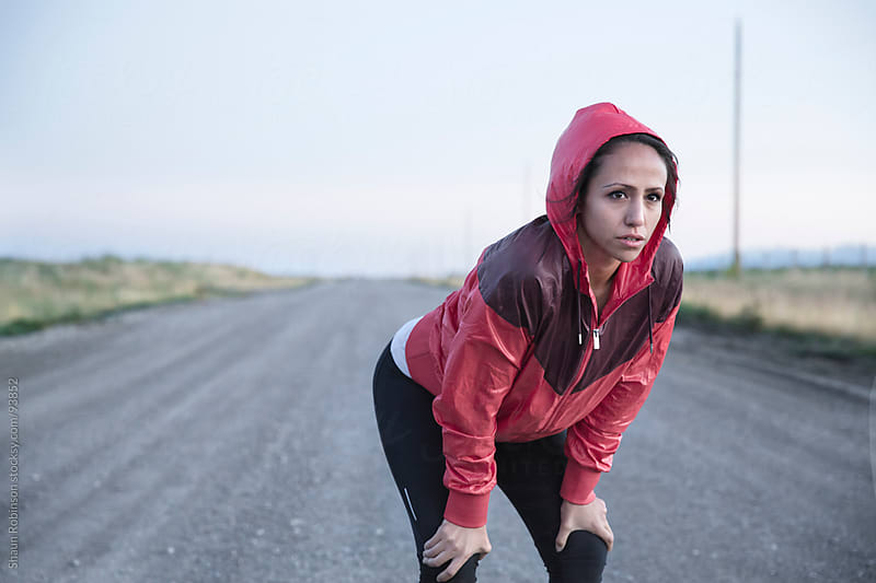 A young fit woman hunched over on a gravel road by Shaun Robinson for Stocksy United