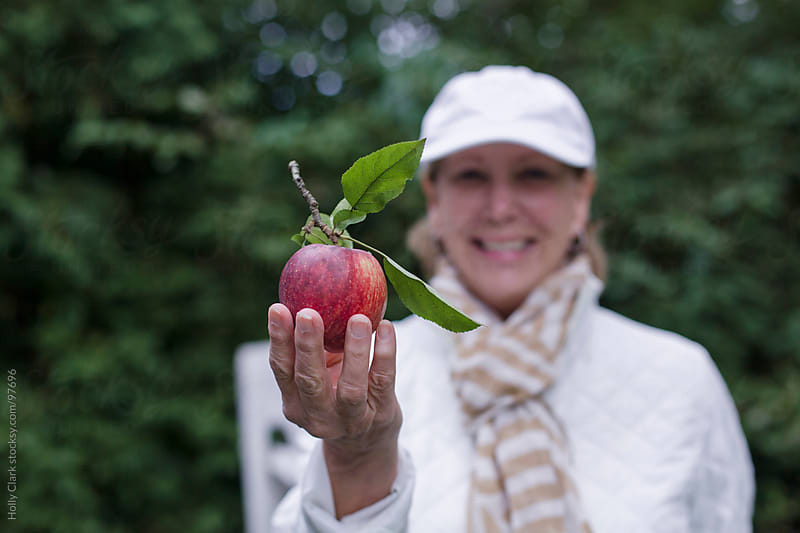 A smiling woman holds an apple out in front of her. by Holly Clark for Stocksy United
