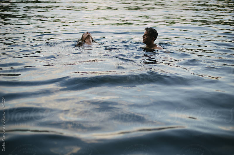 Fun adventurous couple swimming in lake at dusk by Daring Wanderer for Stocksy United