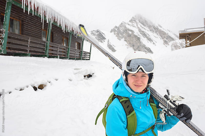 Woman with ski equipment standing in front of the cabin by RG&B Images for Stocksy United