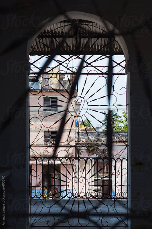 Street facade through a window grille in Cardenas, Cuba by Amanda Large for Stocksy United