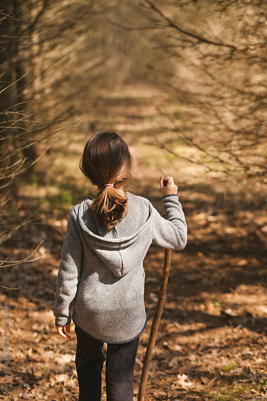 A young girl hiking in the woods with a walking stick by Amanda Worrall for Stocksy United