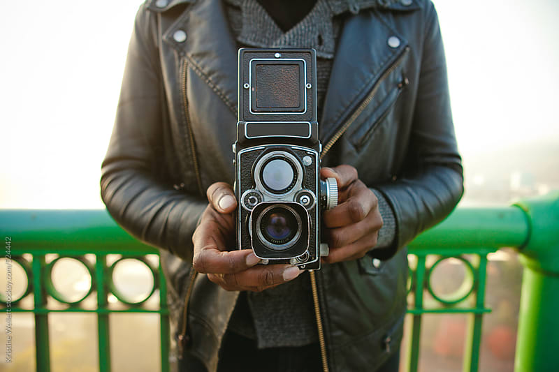 Close up of a hip man holding a vintage twin lens camera by Kristine Weilert for Stocksy United