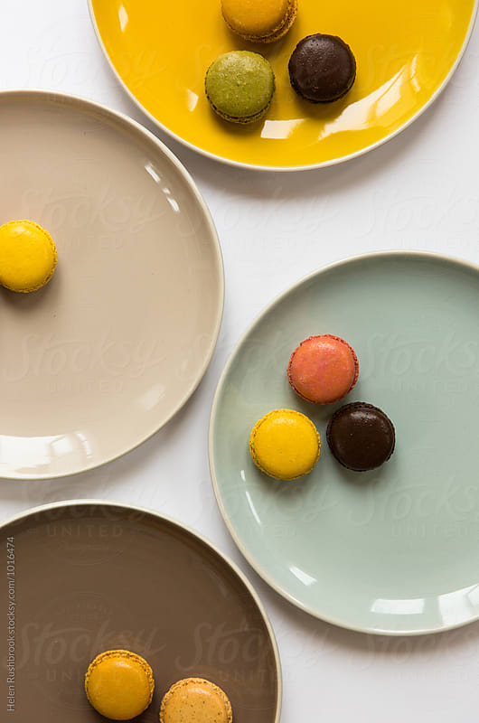 Colourful macaroons on colourful plates. by Helen Rushbrook for Stocksy United
