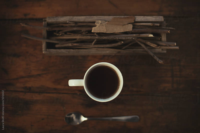 Tea cup, spoon and dried woods seen from above on old wooden table by Laura Stolfi for Stocksy United
