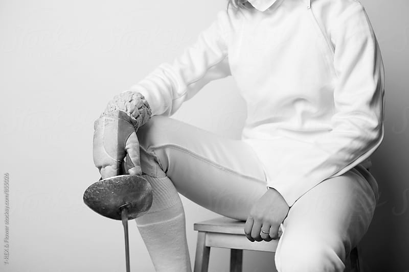 Close-up of female fencer sitting and holding sabre by Danil Nevsky for Stocksy United