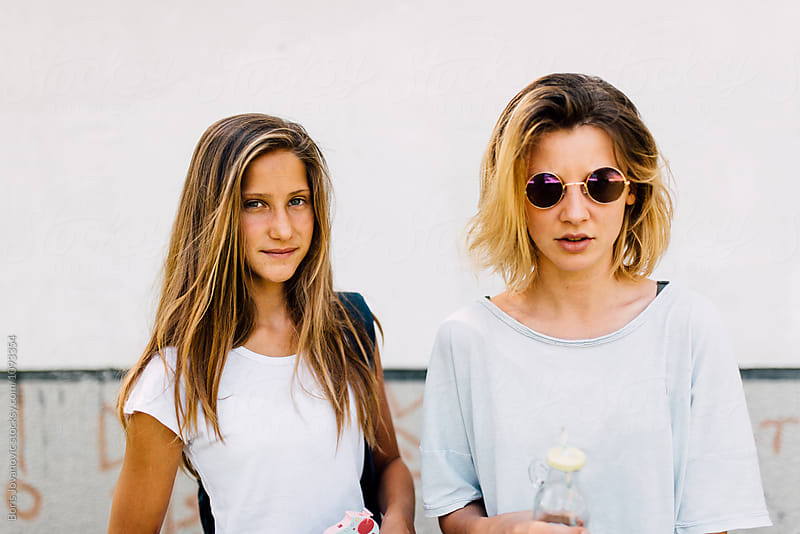 Portrait of a two young girls outdoor by Boris Jovanovic for Stocksy United