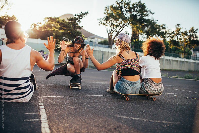 Female skaters giving high five to friends by Jacob Lund for Stocksy United