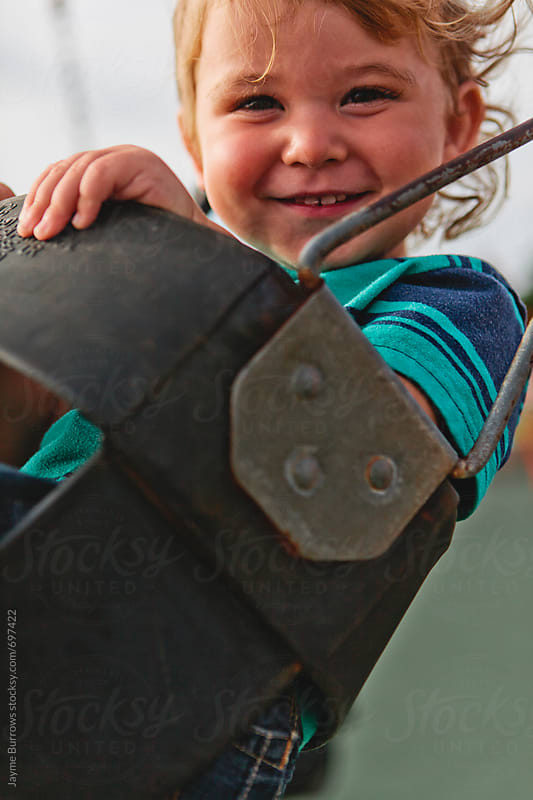 Toddler Playing on Swing by Jayme Burrows for Stocksy United