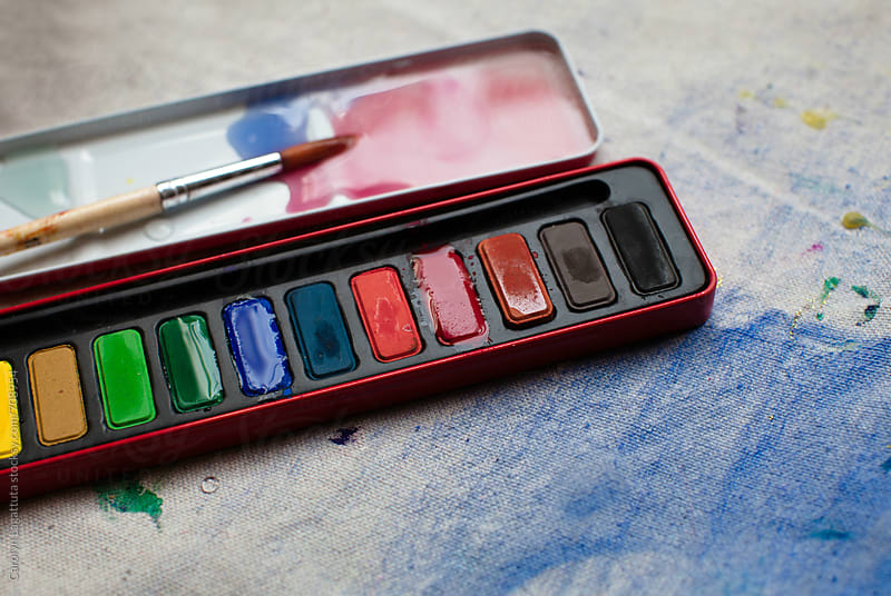 Palette of paints and a paint brush on a canvas by Carolyn Lagattuta for Stocksy United