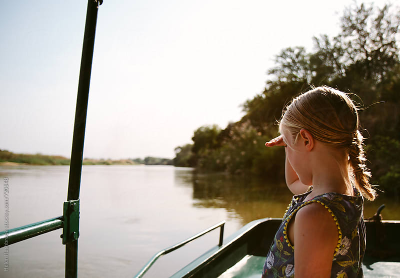 Little girl on a boat on a river looking at nature by Helen Rushbrook for Stocksy United