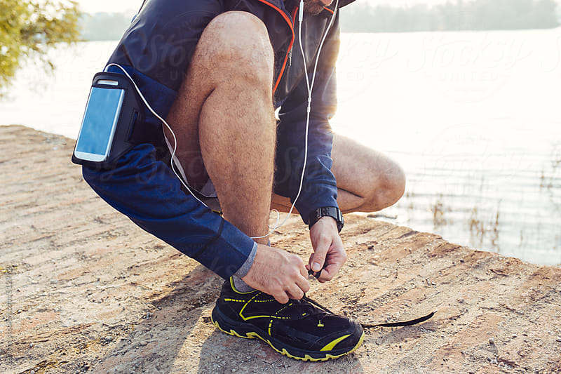 Sporty Man Tying Laces on Running Sneakers by Lumina for Stocksy United