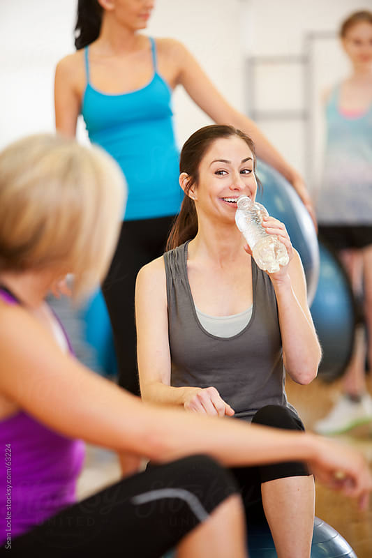 Gym: Woman Drinks Water Before Exercise Class by Sean Locke for Stocksy United
