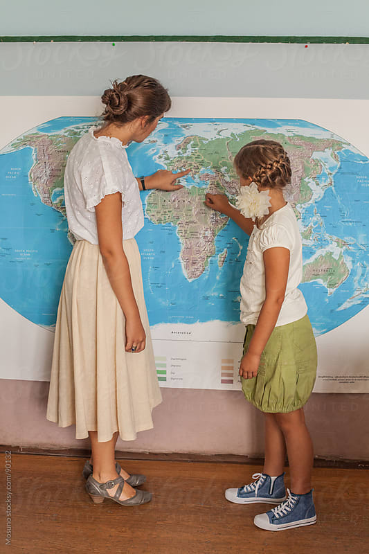 Teacher and a Pupil Looking at the World Map by Mosuno for Stocksy United