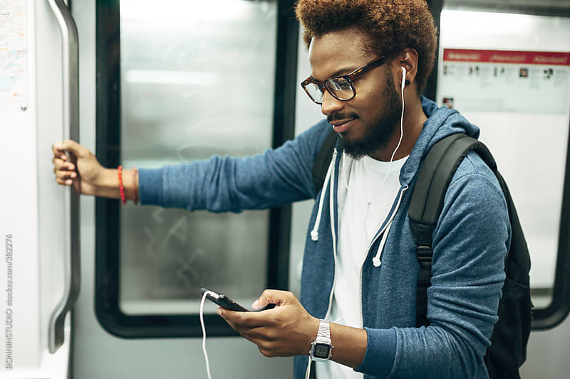 Young afro black man using mobile phone while listening ...