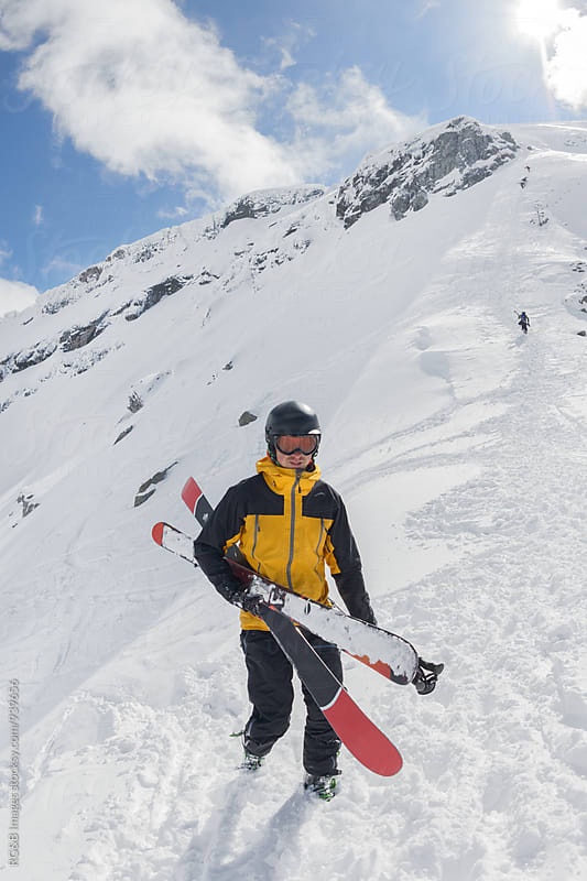 Skier carrying his skis  by RG&B Images for Stocksy United