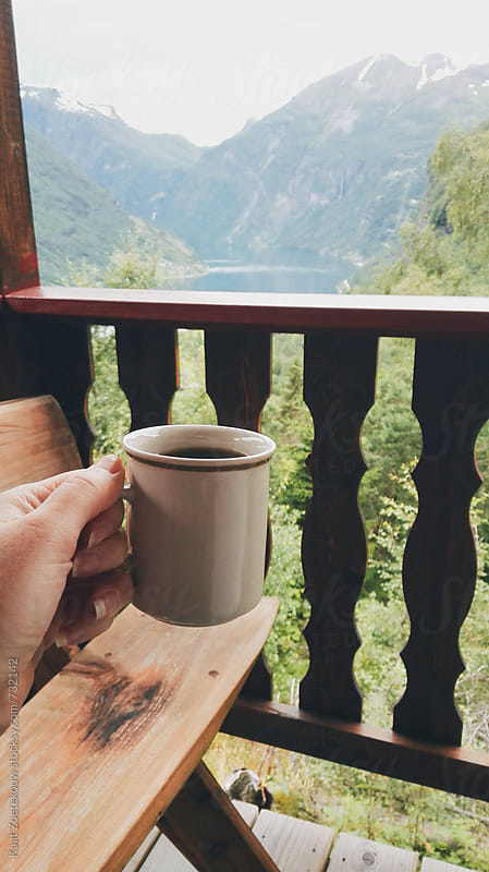 Hand holding out cup of coffee on cabin deck with fjord view by Kaat Zoetekouw for Stocksy United