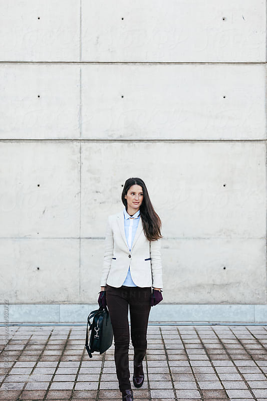 Young businesswoman walking down the sidewalk in the city. by BONNINSTUDIO for Stocksy United