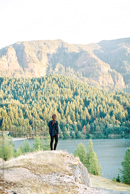 Girl standing at edge of mountain by Daniel Kim Photography for Stocksy United