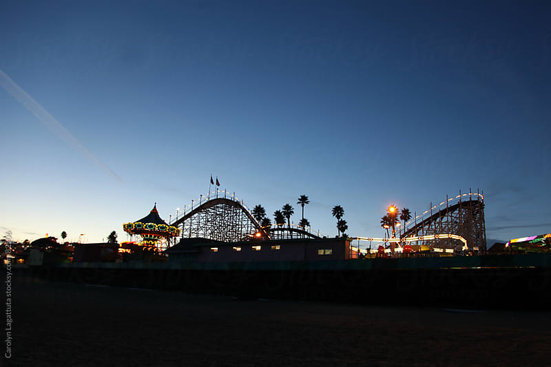 Night time scene of an amusement park on the beach by Carolyn Lagattuta for Stocksy United