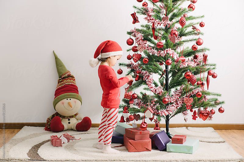 A cute toddler girl decorating christmas tree by MaaHoo Studio for Stocksy United