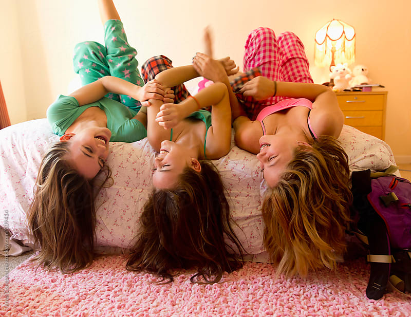 three tweens laying on the bed, having a sleep-over by Tanya Constantine for Stocksy United