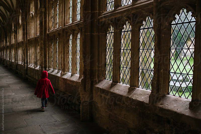 Little girl running in medieval cloisters. by Julia Forsman for Stocksy United