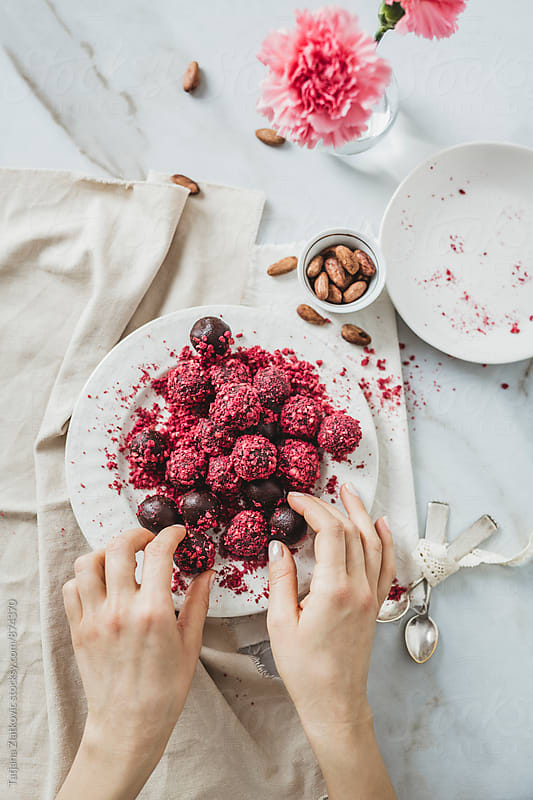Making chocolate truffles with dried raspberries by Tatjana Zlatkovic for Stocksy United