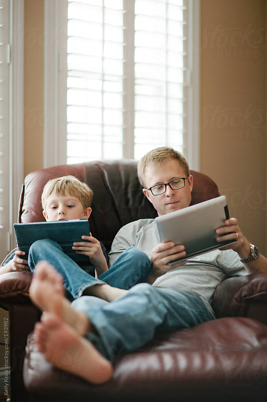 father and child playing games on electronic devices by Kelly Knox for Stocksy United