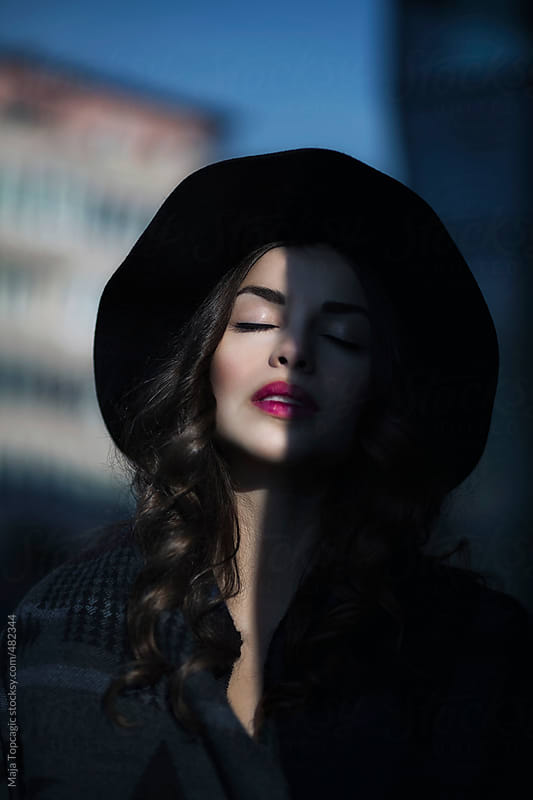 Young beautiful woman with curly hair, hat and red lipstick by Maja Topcagic for Stocksy United