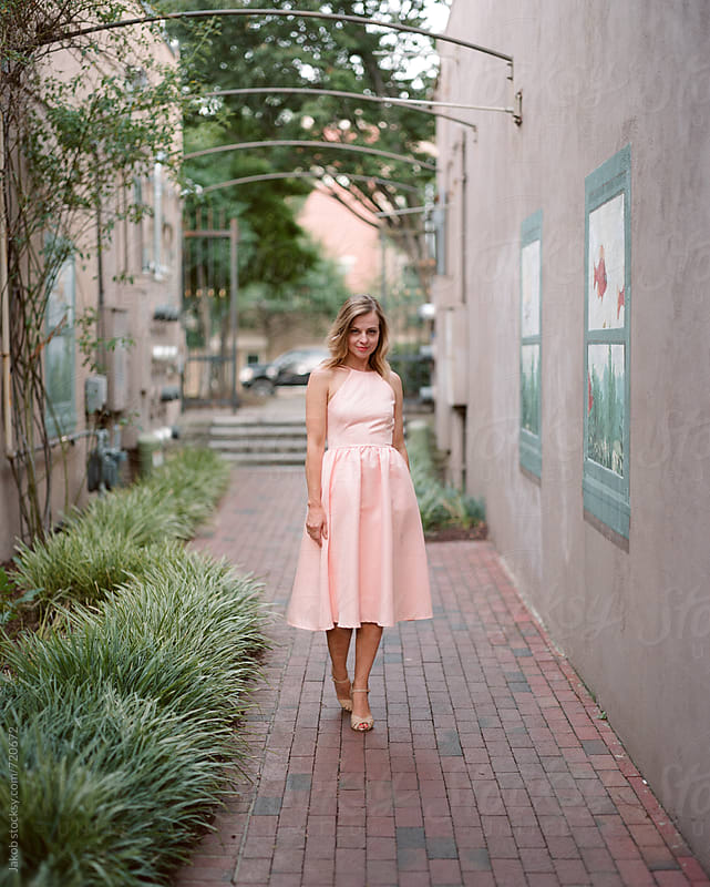 Beautiful and fashionable woman standing in an alleyway  by Jakob for Stocksy United