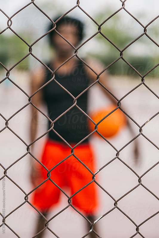 Blurred Basketball Player Behind a Grilled Gate by Victor Torres for Stocksy United