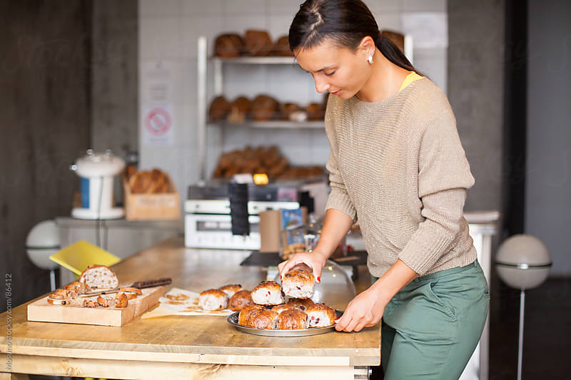 Woman Arranging Pastry in Her Shop by Mosuno for Stocksy United