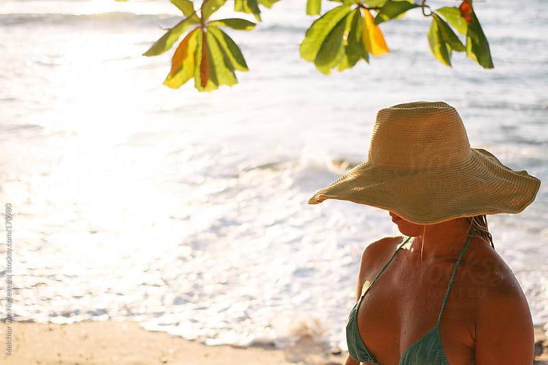 Girl with hat walking on the beach in het bikini by Melchior van Nigtevecht for Stocksy United