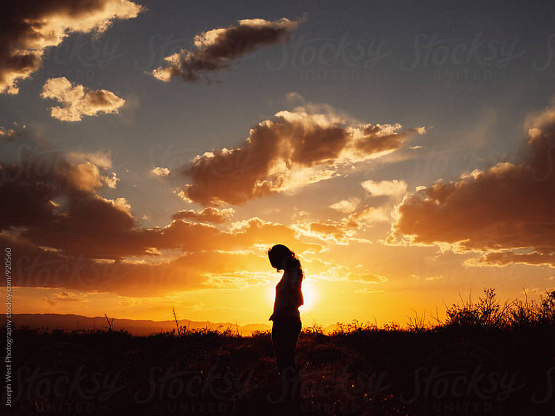 A woman silhouetted by the setting sun by Joseph West Photography for Stocksy United