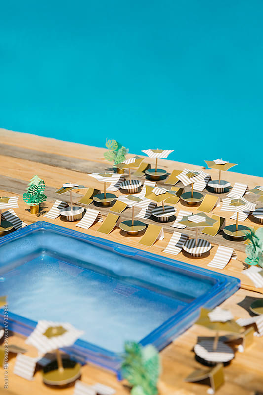 Pool concept,arranged umbrellas and beach chairs in the Summer achieved of  paper craft by Beatrix Boros for Stocksy United
