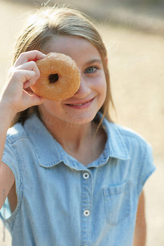 Young girl smiling with a doughnut in front of her face by Miquel Llonch for Stocksy United