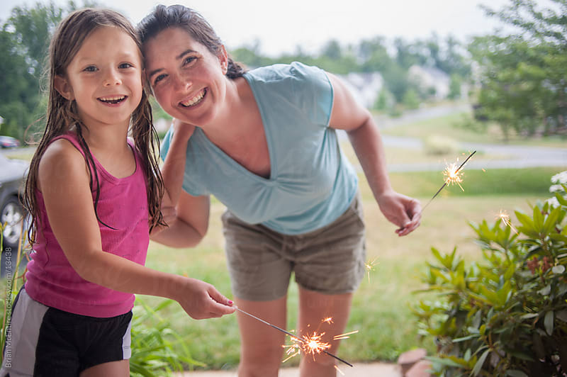 Little girl and mom with lit sparklers by Brian McEntire for Stocksy United