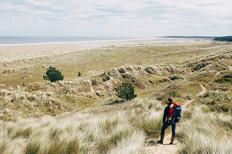 Young father walking on the coast with his daughter in a baby carrier backpack. Norfolk, UK. by Liam Grant for Stocksy United