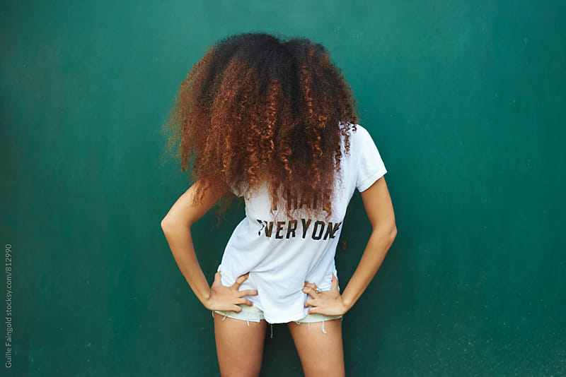 Young Afro-American woman standing with her hands on hips by Guille Faingold for Stocksy United